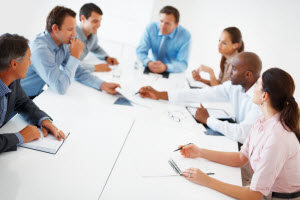 Professionals sit around a conference table.