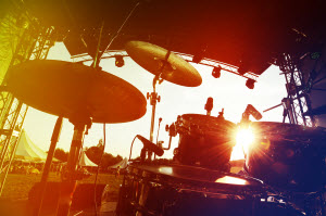 Sunlight shines on a drum set on an outdoor stage.