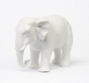 A sculpture of an elephant shows the elephant standing with his trunk curled at the bottom.